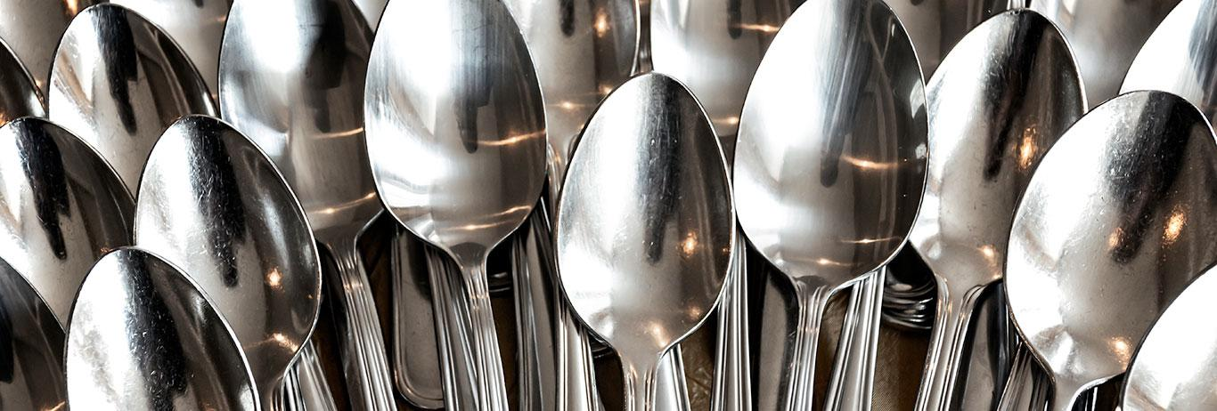 stacked rows of shining silver spoons